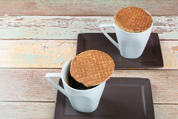 Deux biscuits stroopwafel avec des tasses de café.
