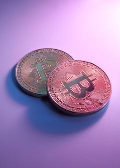 Deux bitcoins dorés isolés sur fond violet rose close-up with copy space