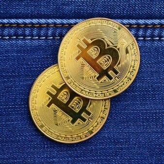 Deux bitcoins dorés reposent sur un tissu de jeans. nouvelle monnaie virtuelle. nouvelle crypto-monnaie sous forme de pièces