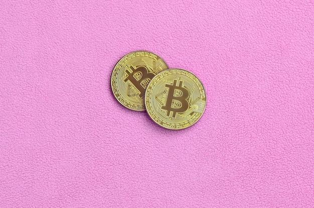 Deux bitcoins dorés se trouvent sur une couverture faite de doux et moelleux