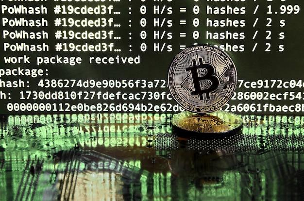 Deux bitcoins se trouvent sur une surface de carte vidéo avec un fond d'écran