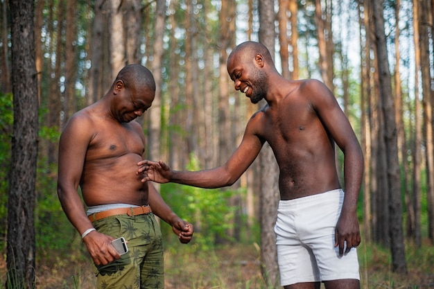 Deux blacks s'amusant et plaisantant debout sans chemise