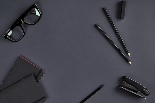 Deux blocs-notes noirs, des lunettes, des crayons et une agrafeuse