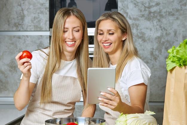 Deux blondes gaies préparent des plats végétariens dans la cuisine et bloguent sur la façon de bien manger