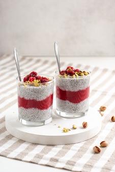 Deux bocal en verre de pudding de chia avec framboise, pistache et confiture rouge sur une table blanche avec nappe à rayures.