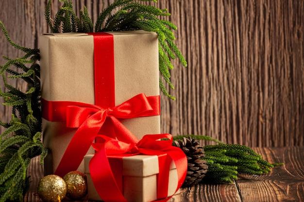 Deux boîtes de cadeau avec noeud de ruban rouge sur fond de bois