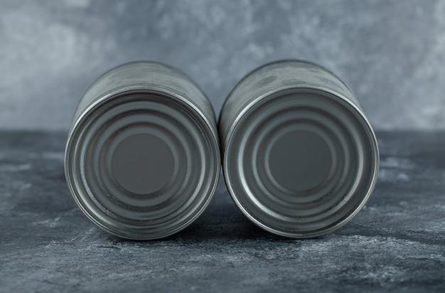 Deux boîtes de conserve placées sur du marbre.