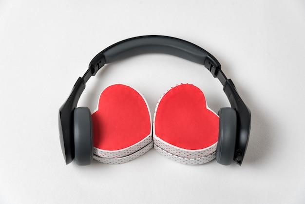 Deux boîtes en forme de coeur et écouteurs sur fond blanc. musique avec amour