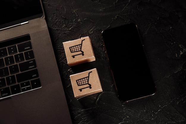 Deux boîtes, ordinateur portable et smartphone sur un gris.