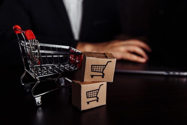 Deux boîtes en papier près du panier. concept d'achat, de commerce électronique et de livraison en ligne