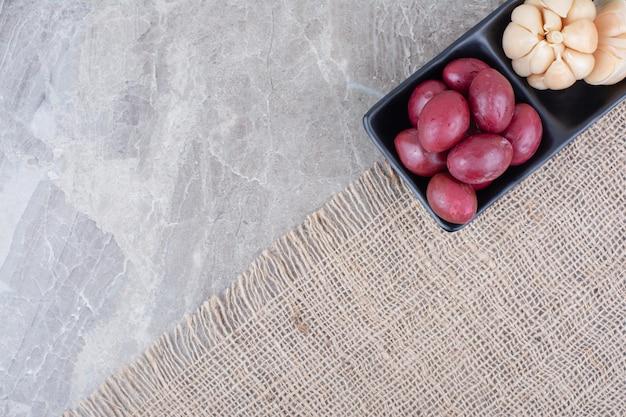Deux bols d'ail mariné et de prunes sur toile de jute.