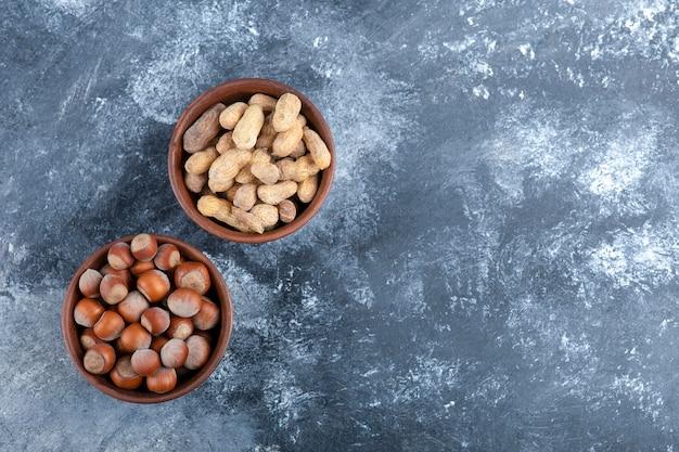 Deux bols d'arachides et de noisettes décortiquées bio sur marbre.