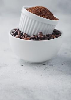 Deux bols l'un sur l'autre avec des grains de café crus frais et de la poudre sur fond de table clair.