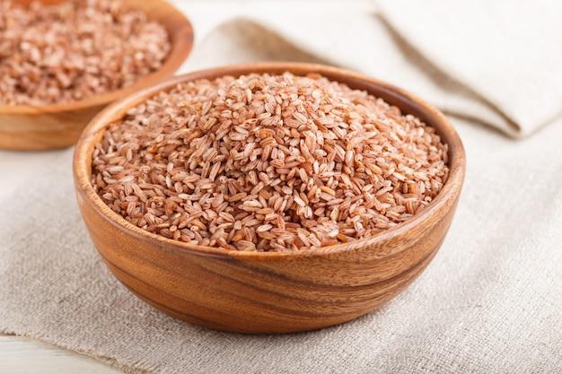 Deux bols en bois avec du riz brun non poli. vue latérale, gros plan.