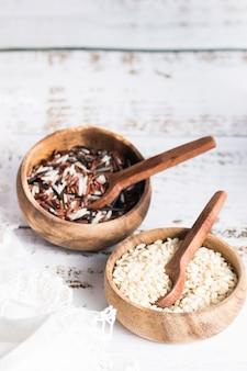 Deux bols en bois avec riz sauvage et riz brun
