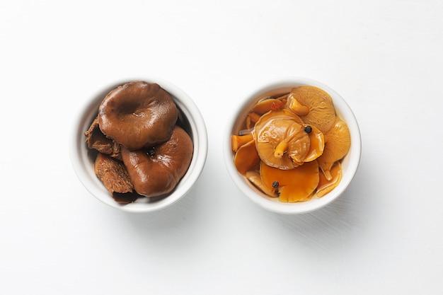 Deux bols en céramique aux champignons marinés.