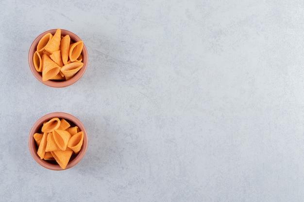 Deux bols de chips croustillantes en forme de triangle sur pierre.