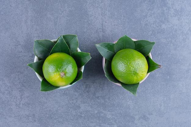 Deux bols de citrons sur table en marbre.