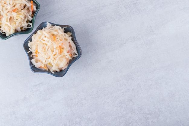 Deux bols de délicieuse choucroute placés sur une table en pierre.