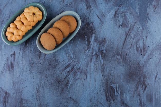 Deux bols de divers biscuits sucrés sur bleu.
