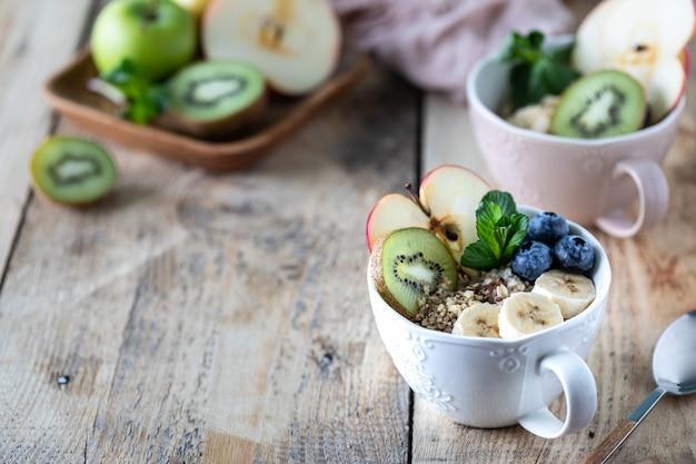 Deux bols de flocons d'avoine ou de granola aux bleuets, pomme, miel et menthe sur un fond en bois rustique. espace copie