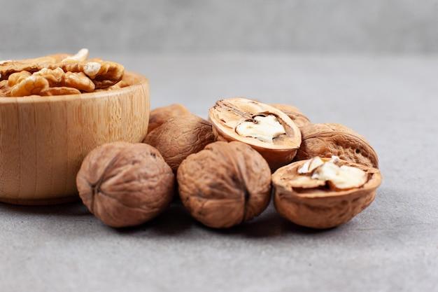 Deux bols de noix entières et craquelées sur une surface en marbre.