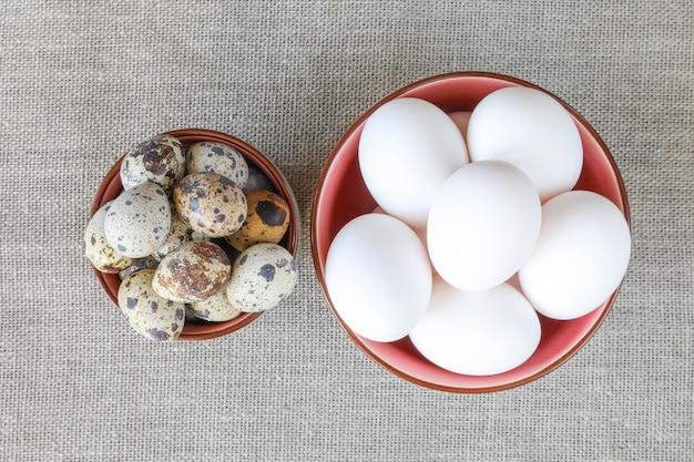 Deux bols d'oeufs de poulet et de caille sur la table