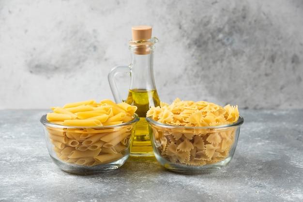 Deux bols de pâtes crues penne et farfalle avec une bouteille d'huile d'olive sur une surface en marbre.