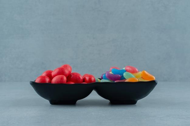 Deux bols pleins de bonbons aux haricots colorés sur une surface blanche