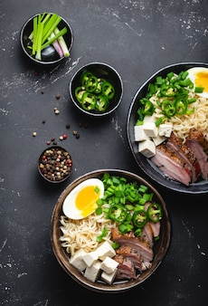 Deux bols de savoureuse soupe de nouilles asiatiques ramen avec bouillon de viande, tofu, porc, œuf avec jaune sur fond de béton rustique noir, gros plan, vue de dessus. soupe de ramen japonaise savoureuse et chaude pour le dîner à l'asiatique