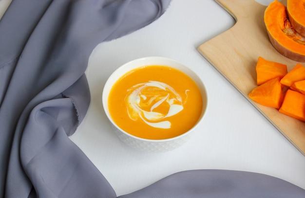 Deux bols de soupe à la citrouille avec du tissu gris et des tranches de courge musquée