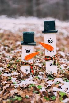 Deux bonhommes de neige en bois dans une forêt