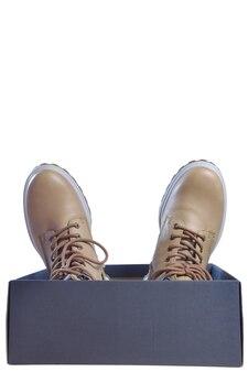 Deux bottes d'hiver beiges à lacets se trouvent dans une boîte avec des chaussettes sur fond blanc sous écrêtage