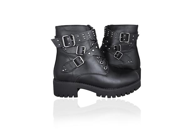 Deux bottes noires à lacets avec boucles et sangles, isolées sur une surface blanche.