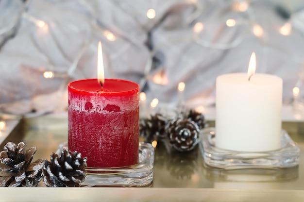 Deux bougies allumées de couleur rouge et blanche et pommes de pin sur plateau en métal doré
