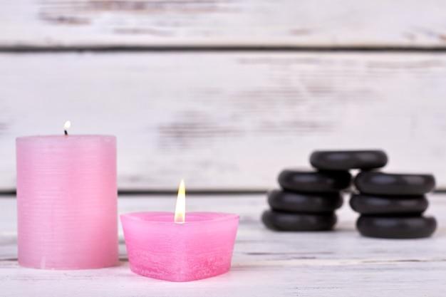 Deux bougies de cire brûlantes et pile de pierres noires de spa