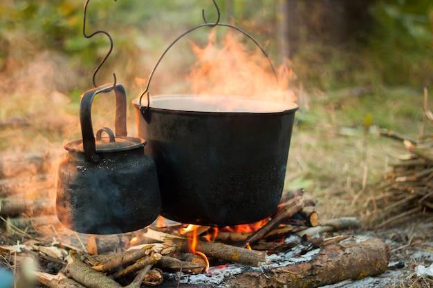 Deux bouilloires touristiques fumées sur feu de camp