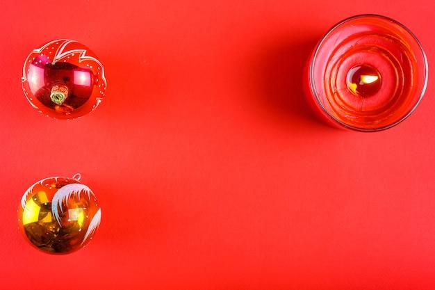 Deux boules de noël et une bougie sur fond rouge avec un espace lance.