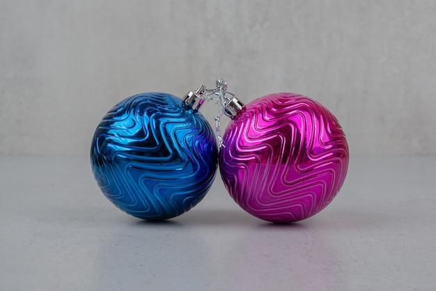Deux boules de noël colorées sur mur gris.