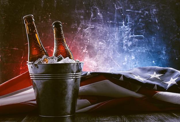 Deux bouteilles de bière dans un seau à glace avec le drapeau américain à proximité. concept de célébration de la fête de l'indépendance