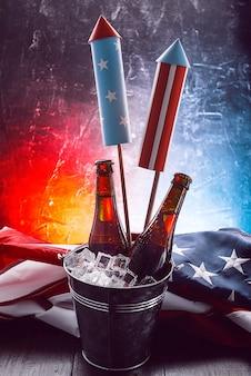Deux bouteilles de bière dans un seau à glace avec le drapeau américain à proximité et des fusées pour les feux d'artifice. concept de célébration de la fête de l'indépendance