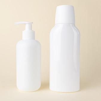 Deux bouteilles cosmétiques blanches sans étiquettes sur beige
