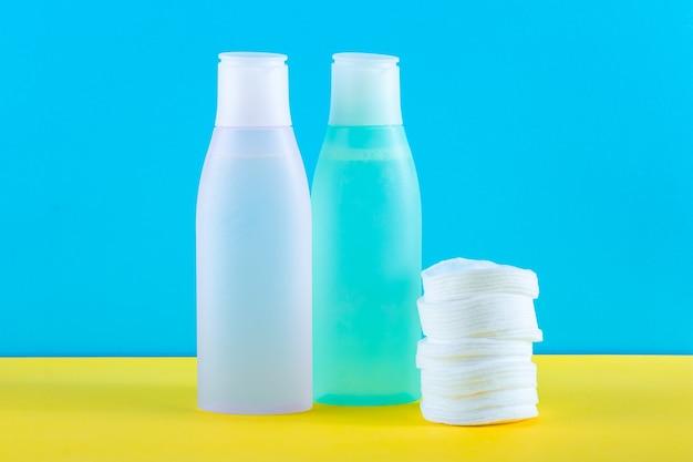 Deux bouteilles cosmétiques avec de l'eau micellaire et des tampons de coton sur fond jaune et bleu