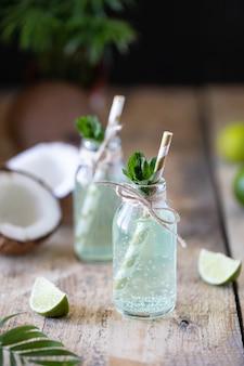 Deux bouteilles d'eau de coco à la menthe et au citron vert sur une table en bois. boisson végétarienne. mojito. espace copie