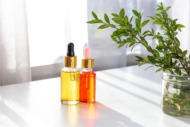 Deux bouteilles de jaune et une bouteille d'huile cosmétique bio rose se tiennent sur un tableau blanc