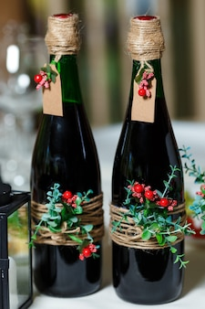 Deux bouteilles de mariage vertes avec du vin rouge décorées de fleurs, de verdure et de ficelle