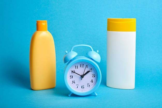 Deux bouteilles de shampooings sans étiquettes et réveil sur fond bleu