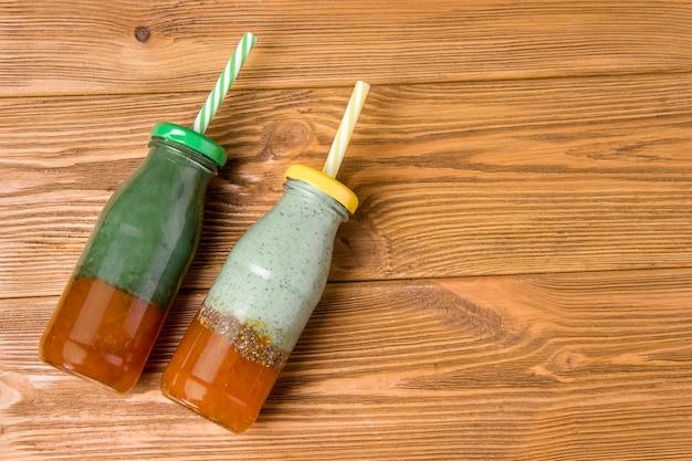 Deux bouteilles de superaliments spiruline boisson aux algues sur une table en bois.