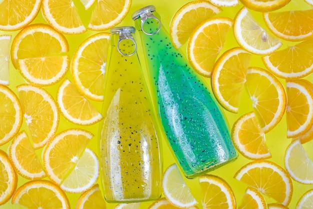 Deux bouteilles en verre sur un fond d'agrumes tropicaux lumineux.