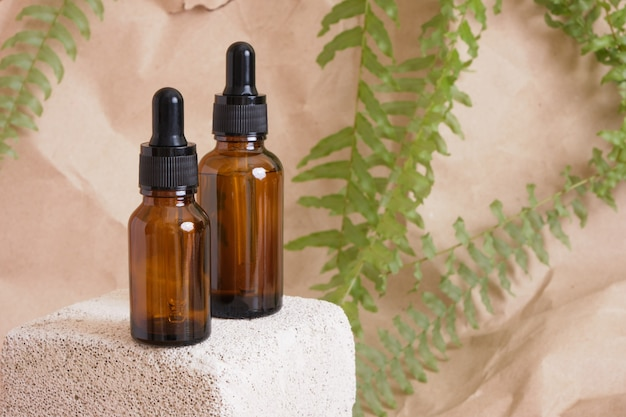 Deux bouteilles en verre marron avec une pipette pour produits cosmétiques sur un bloc de béton